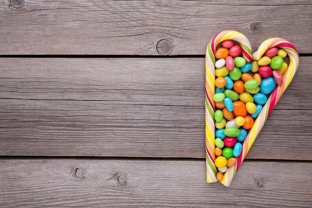 Bunte lutscher und unterschiedliche farbige runde süßigkeit auf grauem hintergrund