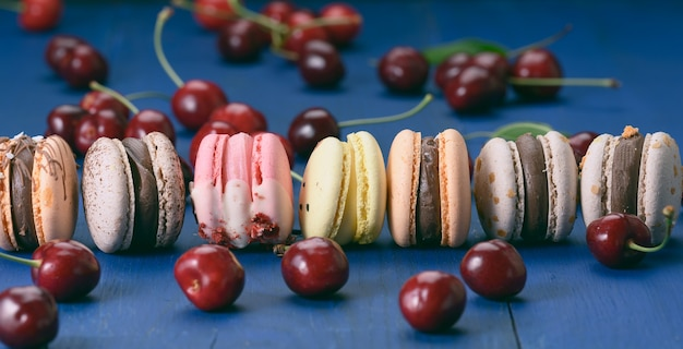 Bunte macarons und reife rote kirschen auf blauem holzhintergrund, nahaufnahme