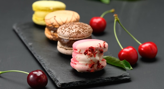 Bunte macarons und reife rote kirschen auf schwarzem holzhintergrund, nahaufnahme