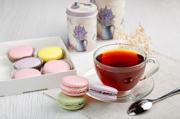 Bunte makronen in einer schachtel und eine tasse tee auf einem hellen holzküchentisch
