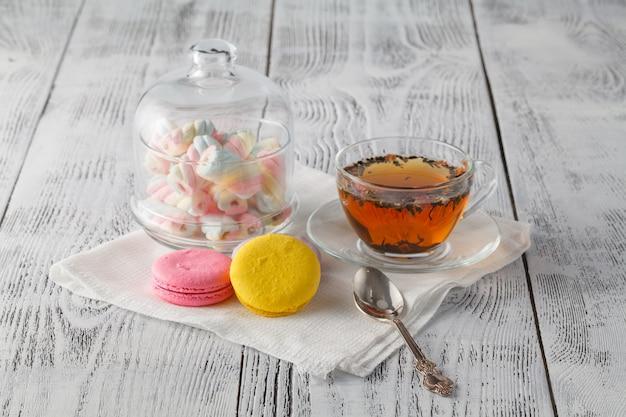 Bunte makronen mit tasse tee auf farbigem holztisch