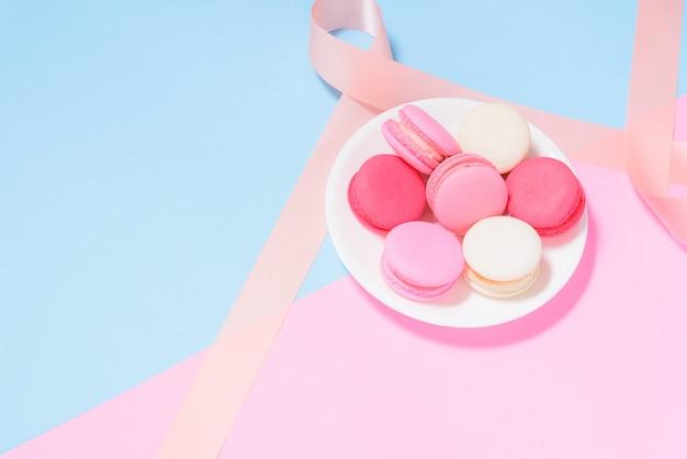Bunte makronen oder macaron auf weißer platte mit rosa band auf rosa und blauem pastellhintergrund