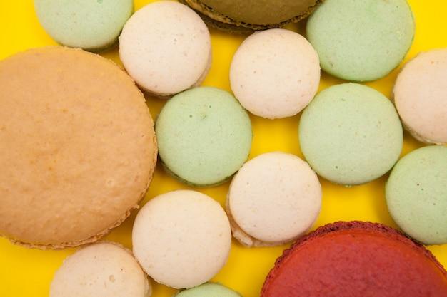 Bunte makronen-plätzchen-kuchen auf gelbem hintergrund. süßes leckeres dessert