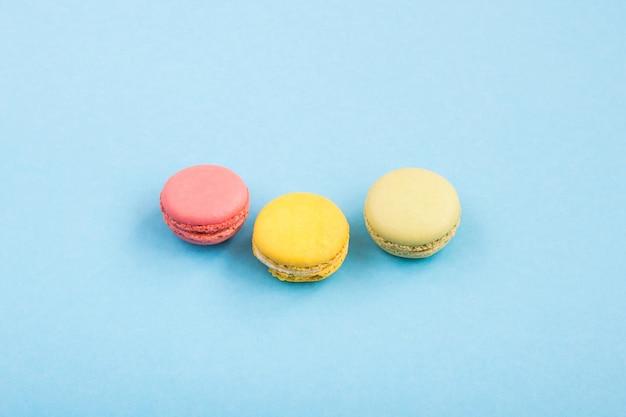 Bunte makronen, rosa, gelbe und grüne makronen auf blauem hintergrund. süßigkeiten, desserts. copyplace, platz für text.