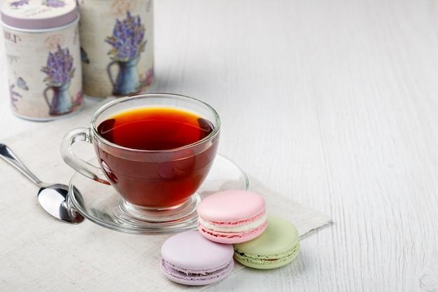 Bunte makronen und eine tasse tee auf einem hellen holzküchentisch