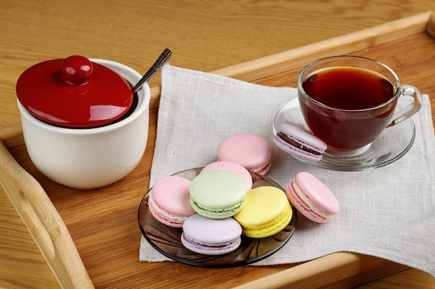 Bunte makronen und eine tasse tee auf einem holztablett