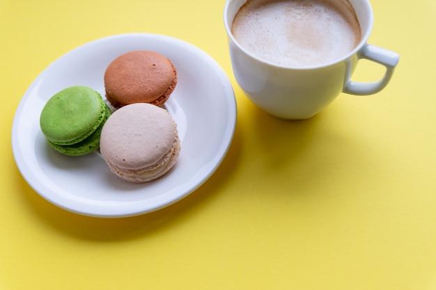 Bunte makronen und kaffee. gebäck, süßwaren und kaffeetasse