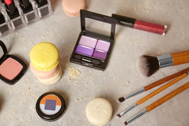 Bunte makronen und schönheitsaccessoires auf dem tisch Premium Fotos