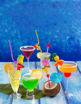 Bunte mannigfaltige tropische cocktails im tropischen blauen holz