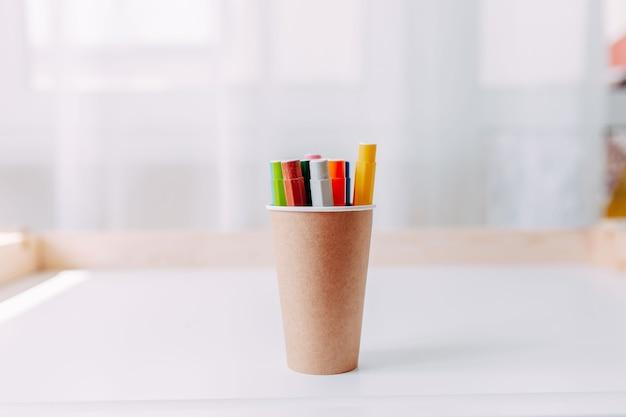 Bunte markierungsstifte im papierpapierglas auf weißem tisch. schulmaterial.