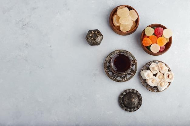 Bunte marmelade erfreut in einer holzschale mit einem glas tee.