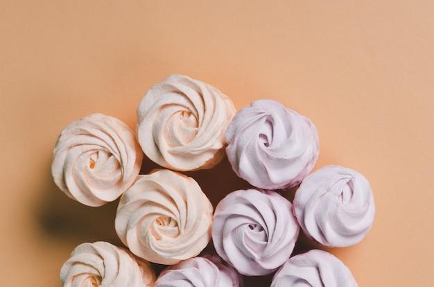 Bunte marshmallows auf pastellhintergrund. färben sie süßen hausgemachten zephyr oder marshmallow.