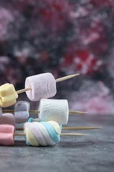 Bunte marshmallows auf stöcken zum grillen.