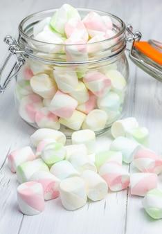 Bunte marshmallows im glas auf hellem hölzernem hintergrund