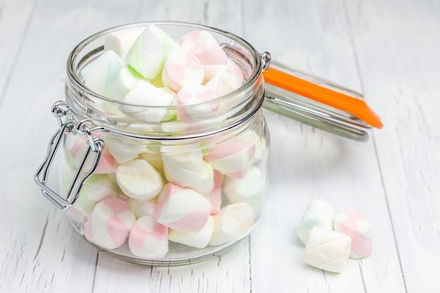 Bunte marshmallows im glasglas auf heller hölzerner hintergrundnahaufnahme