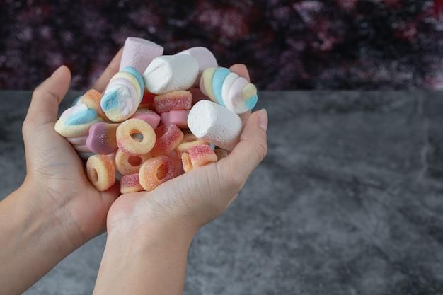 Bunte marshmallows und jellybeans in der hand eines mannes.