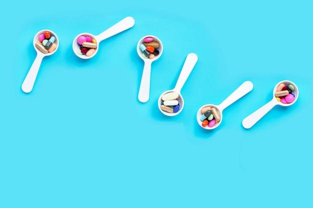 Bunte medizinpillen, -tabletten und -kapseln auf blauem hintergrund