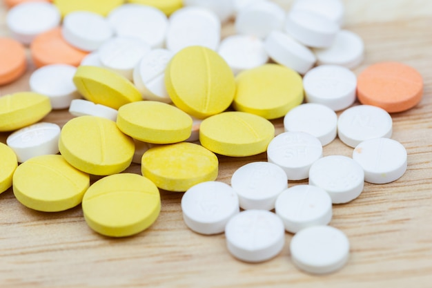 Bunte medizinpillentabletten oder drogennahaufnahme auf hölzernem tabellenhintergrund.