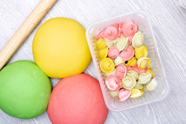 Bunte mehlklöße, pelmeni vom roten, grünen und gelben teig im behälter