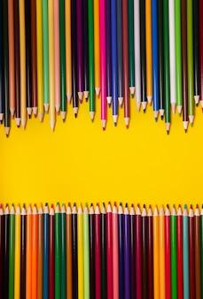 Bunte mehrfarbige stifte auf gelbem hintergrund. draufsicht, kopierraum