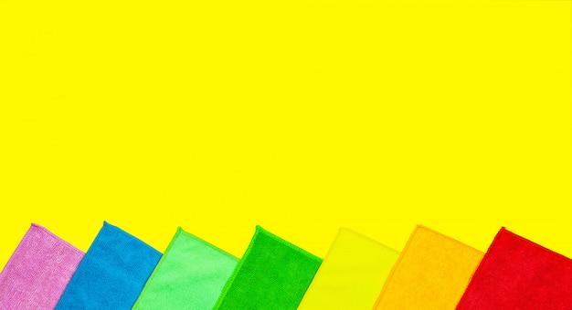 Bunte mikrofaserstaubtücher liegen auf einem hellen gelb