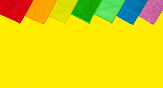 Bunte mikrofaserstaubtücher liegen auf einem hellen gelben hintergrund