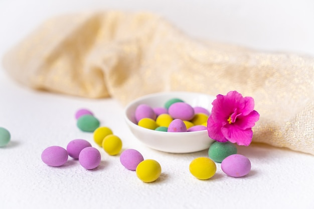Bunte minieier in einer schüssel mit einer rosa blume über einem weißen tisch mit beigem küchentuch