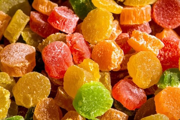 Bunte mischung aus fruchtgelee-süßigkeiten. kandierte früchte im hintergrund. textur der farbigen marmelade. orange-grün-rote bonbons in zucker