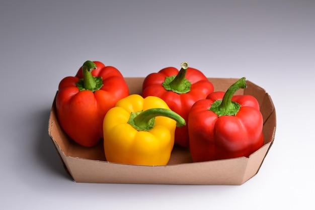 Bunte mischung aus paprika paprika paprika in einem papierbehälter frische bunte paprika box