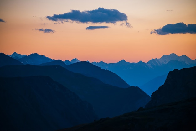 Bunte morgenlandschaft mit schönen bergschattenbildern und goldenem gradientenhimmel mit blauen wolken. lebendige berglandschaft mit malerischem mehrfarbigem sonnenuntergang. panoramablick auf den sonnenaufgang zur bergkette.