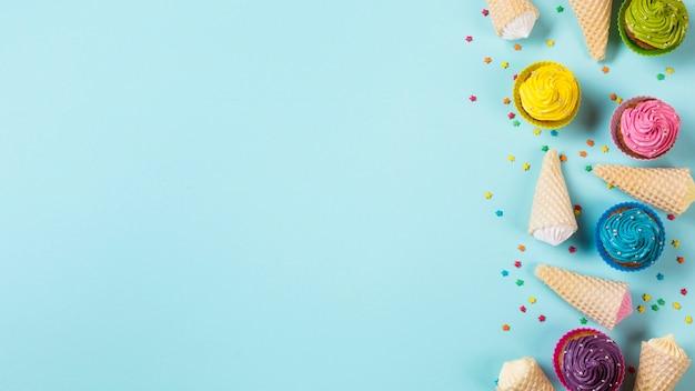 Bunte muffins mit aalaw waffelkegeln und besprüht auf blauem hintergrund