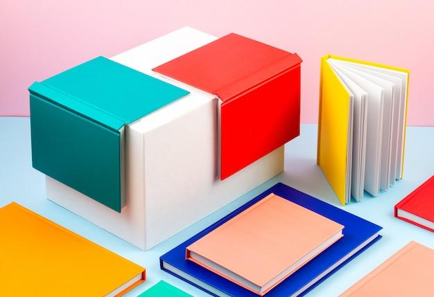 Bunte notizbücher über dem blauen pastellhintergrund. moderner abstrakter arbeitsraum