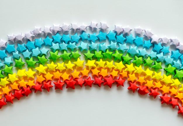 Bunte origami-sterne, die einen regenbogenhintergrund bilden