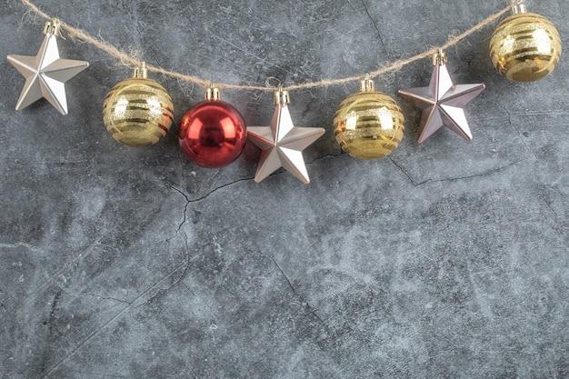 Bunte ornamente aufgehängt aus dem rustikalen faden auf grau
