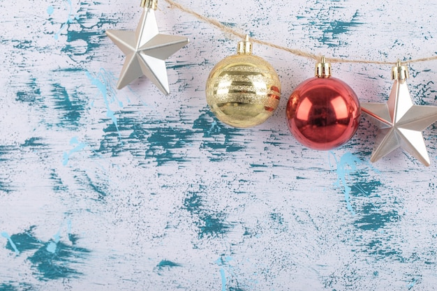 Bunte ornamente hängen am rustikalen faden auf blau-weißem muster