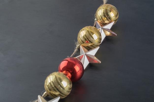 Bunte ornamente hängen aus dem rustikalen faden auf dem dunklen stein