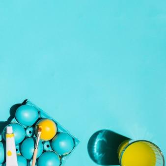 Bunte ostereier im gestell mit pinsel und glas wasser auf tabelle