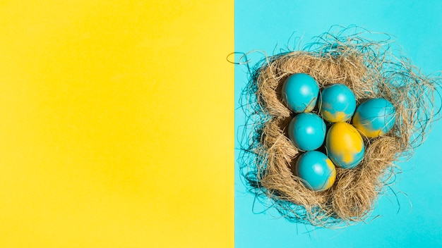 Bunte ostereier im großen nest auf heller tabelle