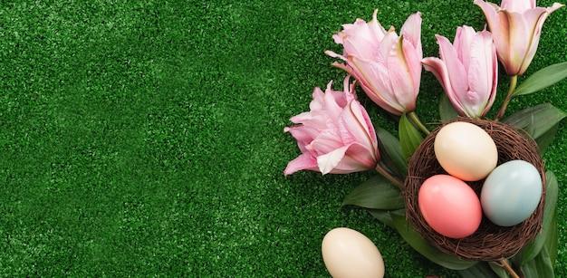 Bunte ostereier im nest mit rosa lilienblume auf einer rasengrasoberfläche.