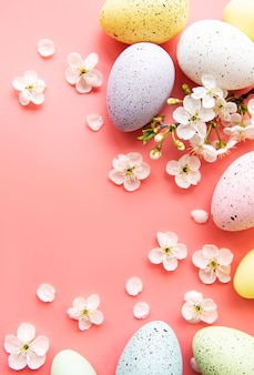 Bunte ostereier mit frühlingsblütenblüten über rosa hintergrund.