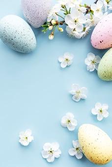 Bunte ostereier mit frühlingsblütenblumen über blauem hintergrund.