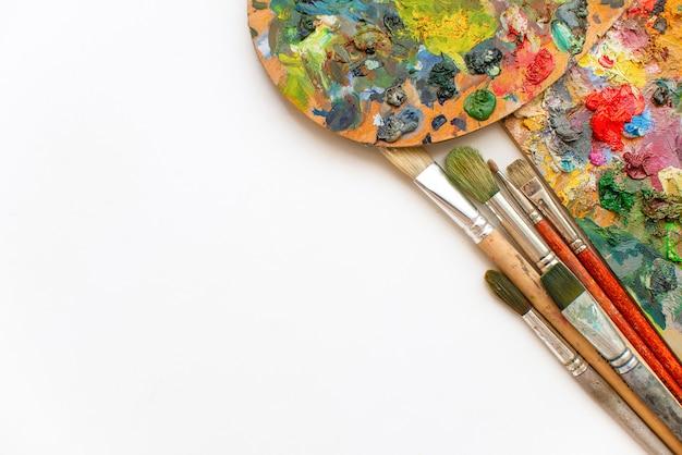 Bunte palette aus holz, pinseln und farbenhintergrund. künstlerisches ölgemälde. künstlerwerkstatt