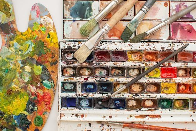 Bunte palette aus holz, pinseln und farbenhintergrund. künstlerisches ölgemälde.