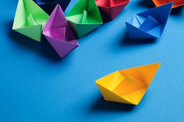 Bunte papierboote auf einer hellblauen oberfläche. speicherplatz kopieren