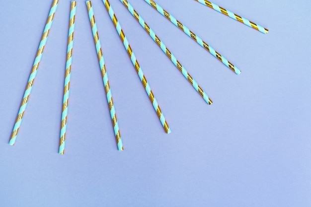 Bunte papiercocktailstrohhalme mit streifenmuster goldfarben für geburtstag oder feiertag. kreative ansicht der feier.
