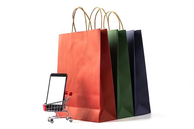 Bunte papiereinkaufstaschen, intelligentes telefon mit leerem bildschirm auf weißem hintergrund