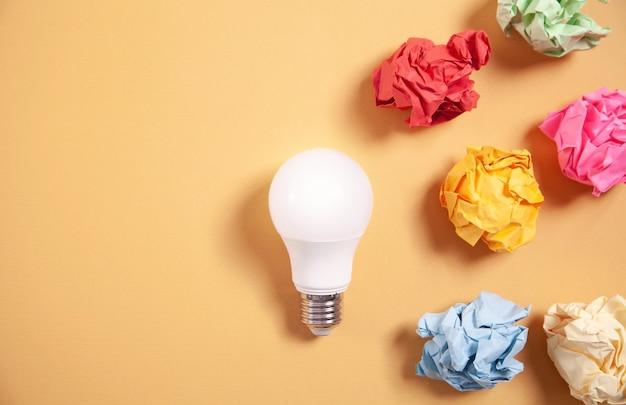 Bunte papierkugeln und glühbirne auf gelbem hintergrund.