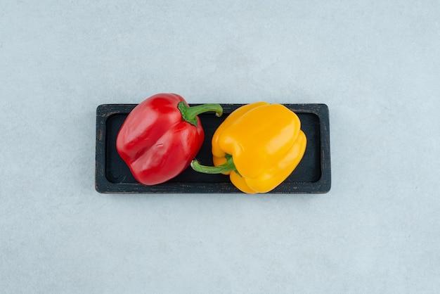 Bunte paprika auf schwarzem teller.