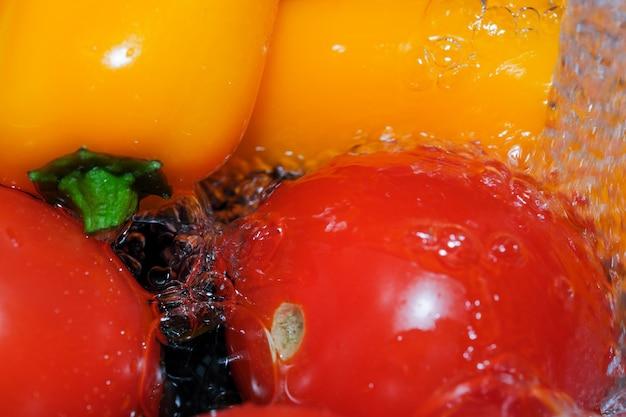Bunte paprika und rote reife tomaten werden in sauberem wasser gewaschen nahaufnahme makrofotografie auf schwarzem hintergrund