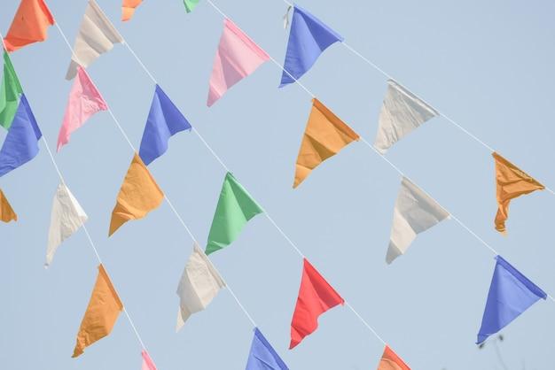 Bunte partei kennzeichnet die flagge, die am blauen himmel für feiertagsdekoration hängt